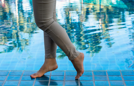 Female legs walking on the swimming pool with green reflection of trees.