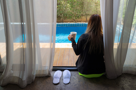 Asian woman sitting on private poolside in the room with white curtains holding white cup in her hand. 免版税图像