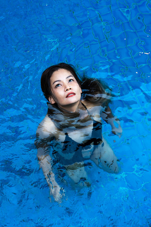 Asian woman in black swimsuit standing in blue swimming pool.