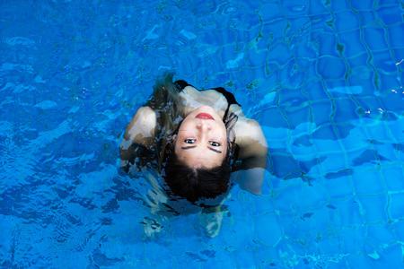 Asian woman in black bikini looking up standing in blue swimming pool.
