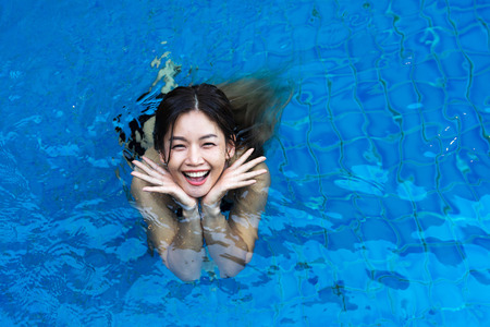 Top view of Asian woman smiling standing in the blue swimming pool.