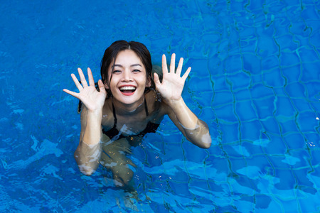 Top view of Asian woman playing happily in the blue swimming pool.