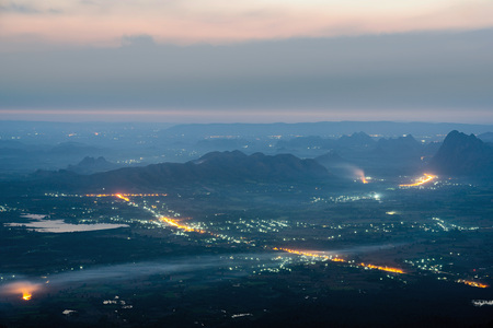 Street lights and small town at dawn with mountain range and agricultural plain near Phu Kradueng, Loei, Thailand.