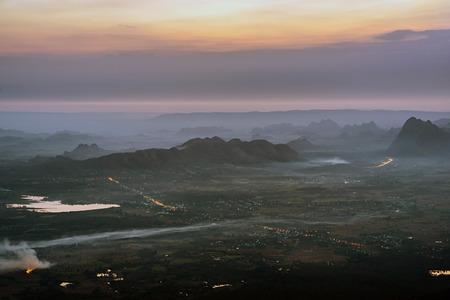 Sunrise with mountain range and street lights in agricultural plain near Phu Kradueng, Loei, Thailand. 版權商用圖片