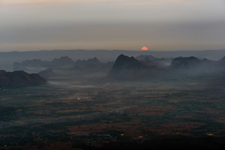 Red sunrise with dark and spooky mountain range with morning fog over agricultural plain.