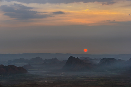 Red sunrise with dark and spooky mountain range and yellow sky with morning fog over agricultural plain. 版權商用圖片