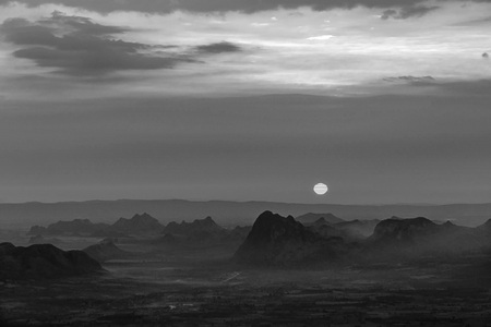 Black and white sunrise with dark and spooky mountain range and bright cloudy sky. 版權商用圖片
