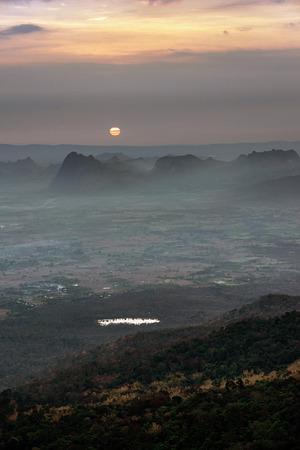Sunrise with morning fog over agricultural plain and dark mountain range near Phu Kradueng, Loei, Thailand.