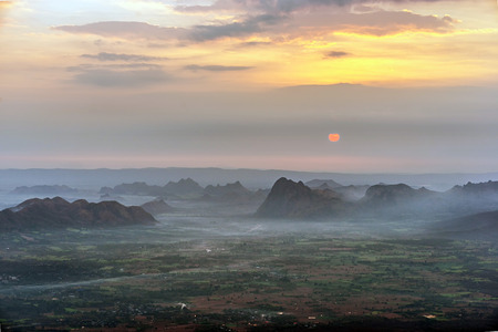 Sunrise and morning fog over agricultural plain and dark mountain range with bright yellow cloudy sky.