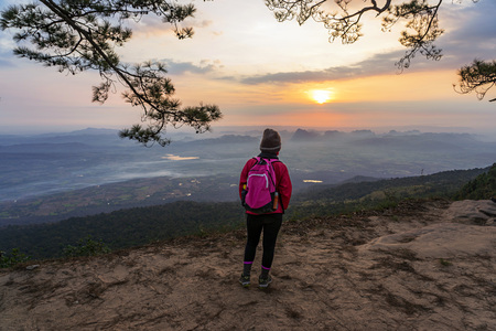 Asian female hiker with pink backpack standing on the cliff looking at mountain sunrise view at Phu Kradueng, Thailand. 版權商用圖片