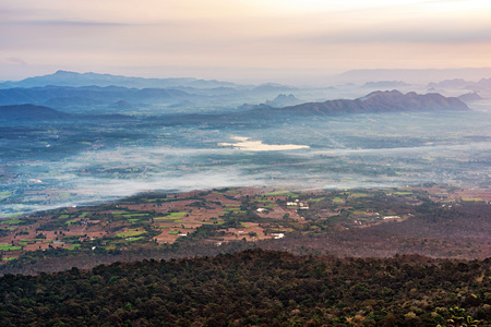 Morning view with dark forest, agricultural farms, fog and mountain range at Phu Kradueng, Thailand. 版權商用圖片
