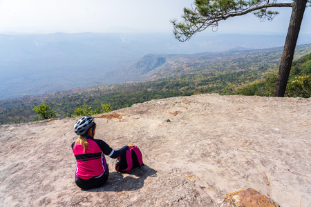 Female cyclist sitting with pink backpack on rock cliff with pine trees and mountain background in Phu Kradueng, Thailand.