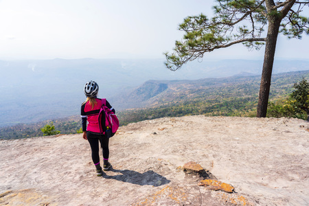 Female cyclist standing on rock cliff with pine trees looking at mountain view at Phu Kradueng, Thailand.