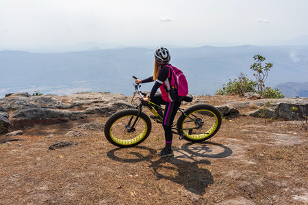 Asian female cyclist on mountain bike looking at mountain range view on rock cliff.