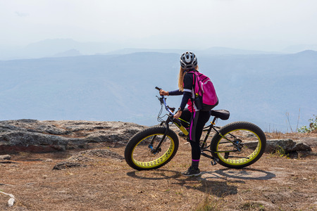 Female cyclist on mountain bike with pink backpack looking at mountain range view from rock cliff in Phu Kradueng, Thailand.