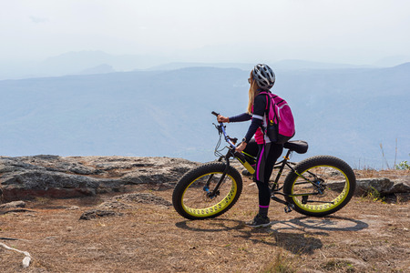 Asian female cyclist resting on mountain bike looking at mountain range view on rock cliff in Phu Kradueng, Thailand.