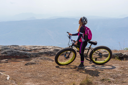 Asian female cyclist standing on mountain bike on rock cliff with mountain background in Phu Kradueng, Thailand.