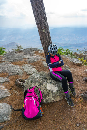 Asian female cyclist resting on rocky cliff under pine tree with mountains background on Phu Kradueng, Thailand.