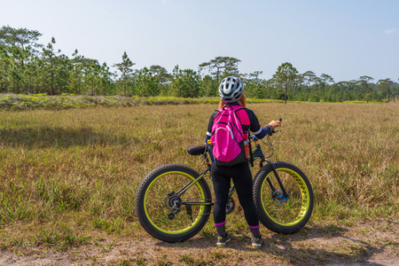 Asian female cyclist standing on grass field with mountain bike and pine trees forest in background.