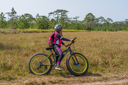 Asian female cyclist standing on mountain bike with grass field and pine trees background.