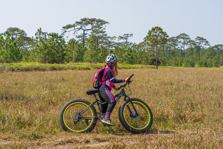 Asian female cyclist standing on mountain bike with grass field and green pine trees background.
