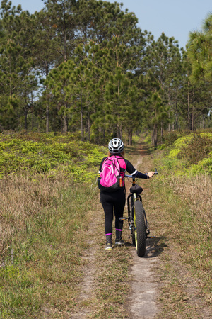 Asian female cyclist walking on dirt road with mountain bike and pine trees forest background.