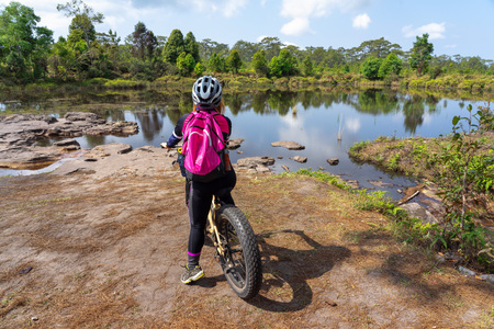 Asian female cyclist standing on mountain bike with lake and pine trees background at Phu Kradueng, Thailand.