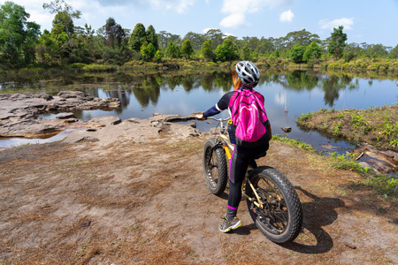 Asian female cyclist with pink backpack standing on mountain bike looking at lake and green forest view.