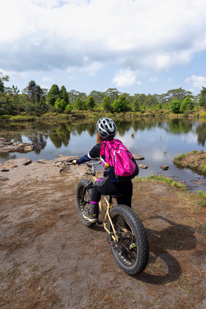 Asian female cyclist standing on mountain bike with lake, trees and sky background.