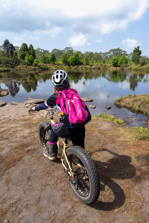 Asian female cyclist with pink backpack standing on mountain bike looking at lake and forest view at Phu Kradueng, Thailand.