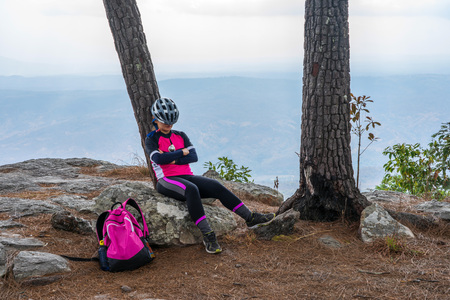 Asian female cyclist sleeping on pine tree and rocky cliff with mountain background.
