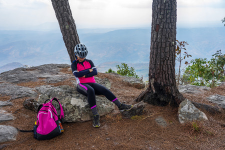 Asian female cyclist sleeping on rocky cliff under pine tree with mountain range background on Phu Kradueng, Thailand.