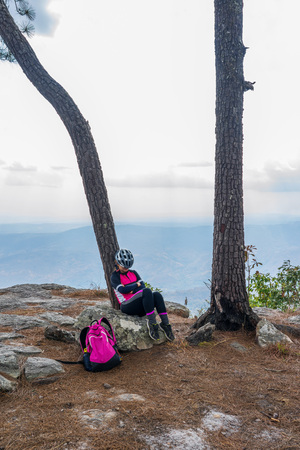 Asian female cyclist sleeping under pine tree on rock cliff with mountain background on Phu Kradueng, Thailand.