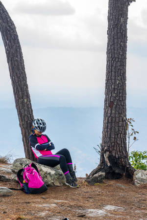 Asian female cyclist sleeping on rocky cliff leaning on pine tree with mountain and sky background on Phu Kradueng, Thailand.