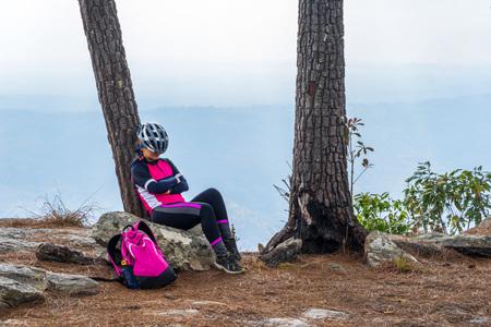 Asian female cyclist sleeping on rocky cliff under pine tree on Phu Kradueng, Thailand.