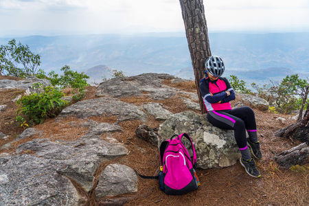 Asian female cyclist resting under pine tree on rocky cliff with mountain range background. 版權商用圖片