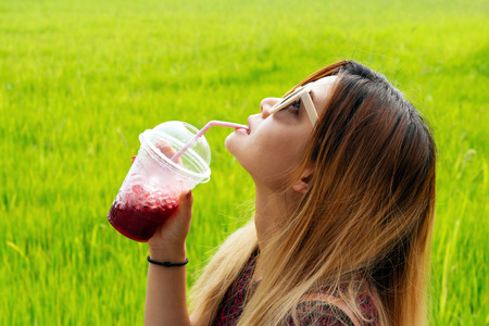 Asian woman with sunglasses looking up drinking red juice with green rice field in the background. 版權商用圖片
