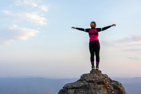 Asian woman standing on high rock cliff with horizon over land and sky background.