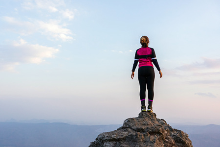 Asian woman in sportswear standing on high rock cliff with horizon over land and sky in the background.