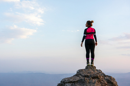 Asian woman in pink sportswear standing on high rock cliff with horizon over the mountain range and sky in the background. 版權商用圖片