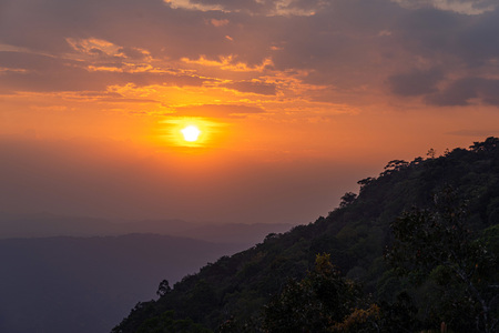 Silhouette of mountain and forest at orange sunset in Phu Kradueng, Thailand.