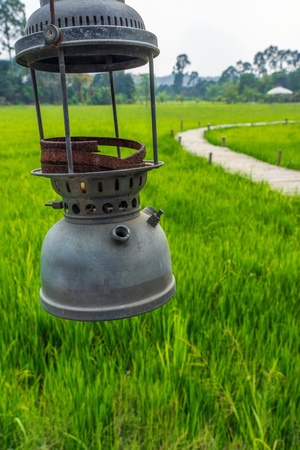 Old lantern hanging with green rice field and bamboo bridge background.