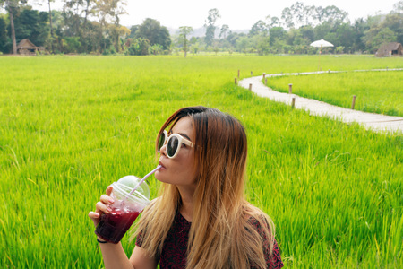 Asian woman wearing sunglasses drinking red juice with green rice field in the background. 版權商用圖片