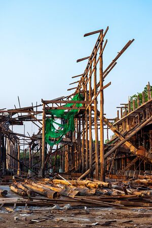 Wood frame construction and log piles of an old demolished rice mill in Thailand. Imagens