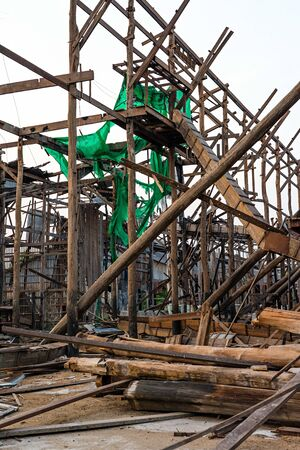 Wooden construction frame and log piles of an old demolished rice mill in Thailand.