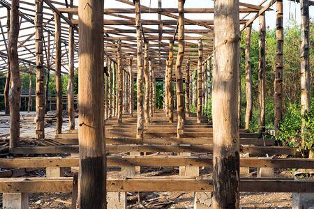 Wooden construction frame with logs and timber from an old deconstructed rice mill warehouse in Thailand. Zdjęcie Seryjne