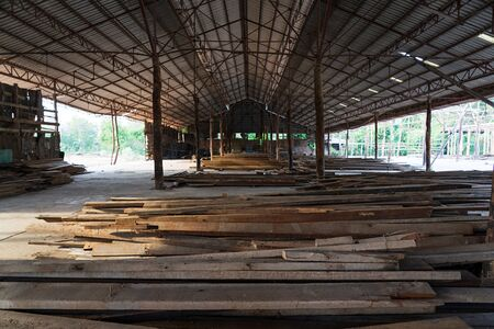 Piles of wooden planks in the open warehouse near wood frame construction site. Imagens
