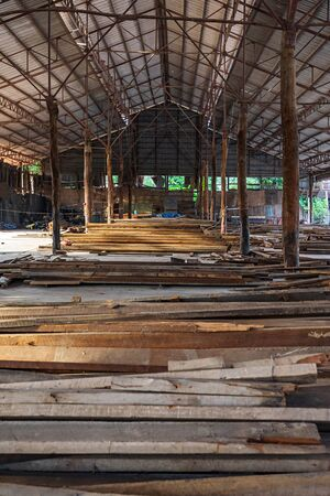 Piles of wooden planks in the large old open warehouse.