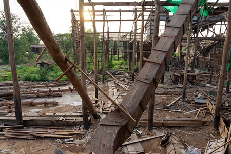 Wooden construction frame and timber piles of an old demolished rice mill in Thailand at sunset.