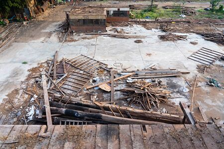 Piles of wood and garbage at demolished old rice mill in Thailand.
